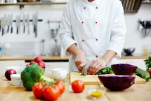 Chef of restaurant cooking fresh vegetable salad from green and red vegs